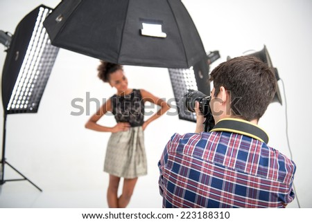 Selective focus on the photographer wearing nice checked shirt standing back to us animated his work photographing the model on background - stock photo
