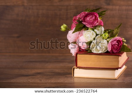 Selective focus on the pile of books with the flowers on the top of it lying on the wooden surface - stock photo