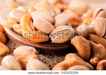 Selective focus on the pistachio and cashew nuts on ladle  - stock photo
