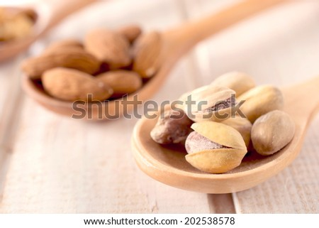 Selective focus on the pistachios in wooden ladle - stock photo