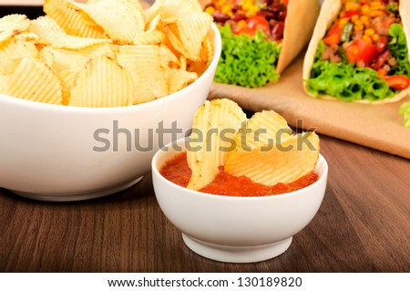 Selective focus on the potato chips in the salsa sauce - stock photo