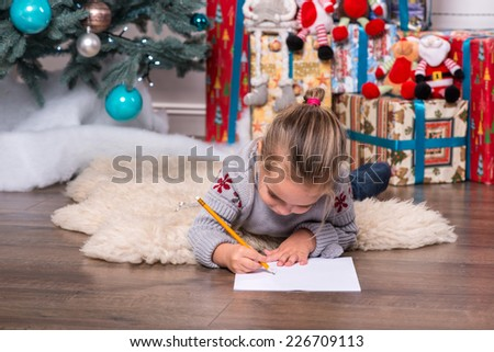 Selective focus on the pretty little fair-haired girl wearing warm sweater and jeans lying on the floor near the Christmas tree writing very diligently something