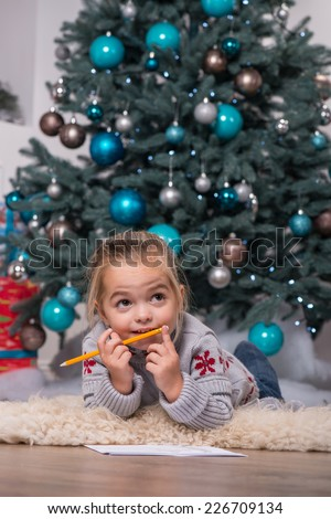 Selective focus on the pretty little fair-haired girl wearing warm sweater and jeans lying on the floor near the Christmas tree with the pencil and paper thinking about something waiting for Santa - stock photo