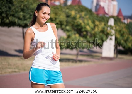 Selective focus on the pretty young smiling woman wearing white T-shirt and blue shorts standing with the bottle of water satisfied with her life