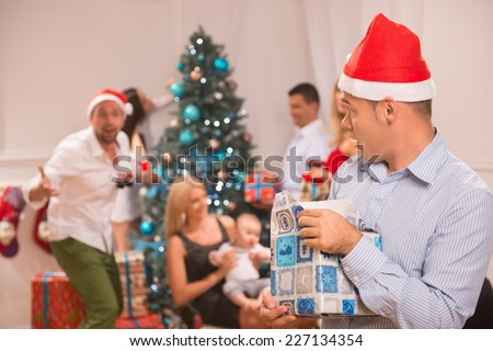 Selective focus on the sly funny guy wearing red cap of Santa Claus standing alone with the present denying giving it back. His friends near the Christmas tree on background - stock photo