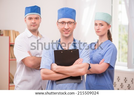 Selective focus on the smiling doctor wearing eyeglasses and blue medical dress keeping a stethoscope on his shoulders and holding a folder. Two his colleagues on background