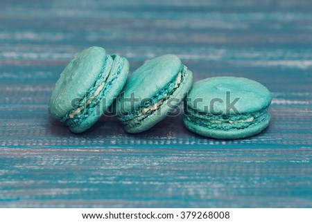 selective focus on three french cookies lying on the textural blue table