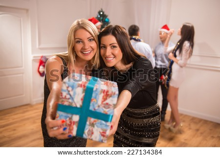Selective focus on two happy smiling friends standing together showing us their present. Their friends celebrating New Year on background - stock photo