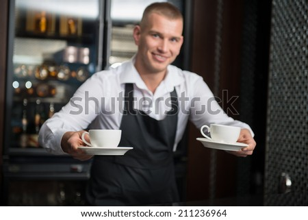 Selective focus on two white cups in the hands of handsome young smiling barista wearing white shirt and black apron suggested us to taste his coffee on background - stock photo