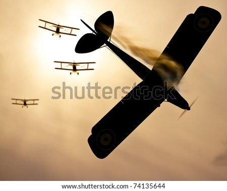 Selective focus on vintage plane of fire.  Three world war one double wing biplanes coming out of the sun to shoot down enemy plane.  Original Illustration - stock photo