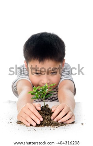 Selective focus on young hand holding the little plant seedling from the black soil and out focus boy face. Concept earth day. - stock photo