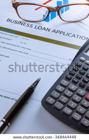 selective focus pen,Business loan application form,chart,glasses ,calculator,red paper clip on wood background.