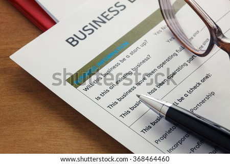 selective focus pen,Business loan application form ,glasses,paper clip on wood background.