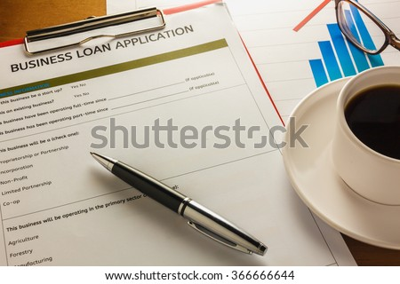 selective focus pen,Business loan application form ,summary chart black coffee,paper clip on wood background. - stock photo