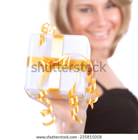 Selective focus photo of a happy smiling female holding in hands little gift box with golden ribbon, Christmas celebration, winter time holidays concept - stock photo
