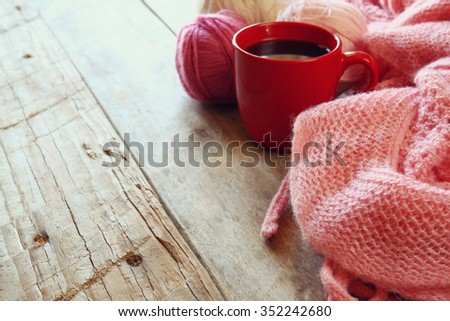 selective focus photo of pink cozy knitted scarf with to cup of coffee and wool yarn balls  on a wooden table - stock photo