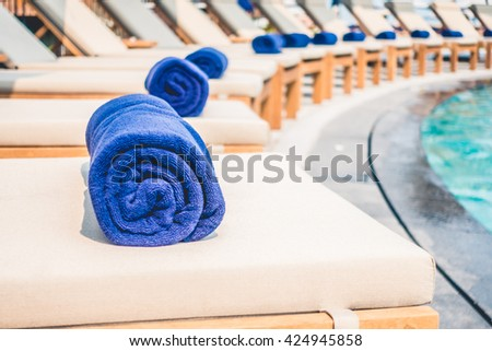 Selective focus point at towel pool on bed around swimming pool in hotel resort - Vintage Light filter - stock photo