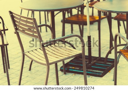 Selective focus point on Chair in coffee shop outdoor zone - vintage filter effect