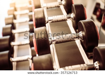 Selective focus point on Dumbbell equipment in fitness gym - Vintage filter