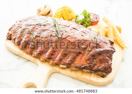 Selective focus point on Grilled rib barbecue pork with sweet sauce and vegetable and frech fries on wooden cutting board