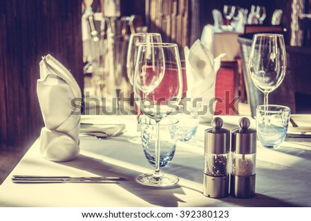 Selective focus point on wine glass with table setting for dinning in hotel restaurant - Vintage Light Filter