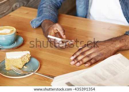 Selective focus. Portrait of African American man wearing denim jacket typing a message or checking email on smart phone while spending leisure time having cappuccino and dessert at a restaurant - stock photo
