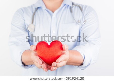 Selective Focus : Portrait of unknown male cardiologist doctor holding his stethoscope, hold red heart . On gray background with shadow - stock photo