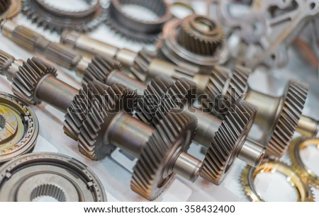 Selective Focus Shiny Gears And Shafts On White Floor - stock photo