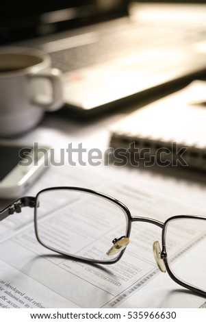 Selective focus table : Businessman hand write notebook, mobile phone, laptop, and pen on the wooden table.working Business concept with effect light added