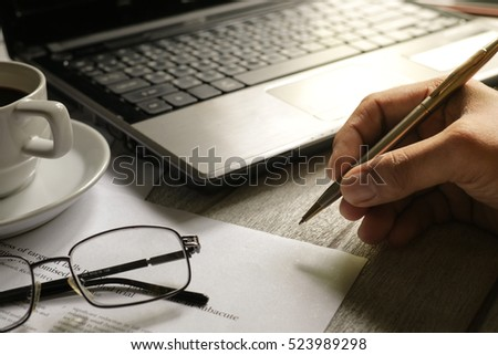Selective focus table : Businessman use pen with eyeglass, mobile phone,laptop, note book on the wooden table.working Business concept with effect light added