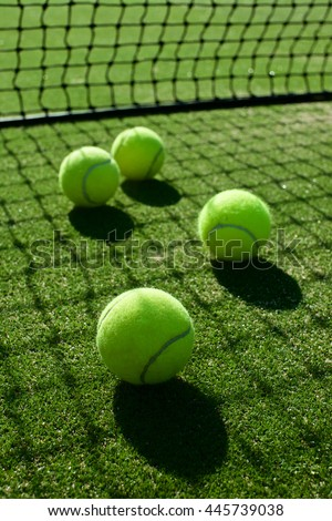 selective focus. tennis ball back light shadow on tennis grass court good for background - stock photo