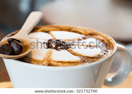 selective focus Top of view cappuccino coffee focus at white foam with wood spoon - stock photo