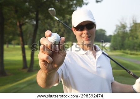 Selective focus view of a smiling young Caucasian male golfer holding a ball out in front of him while also holding a club - stock photo