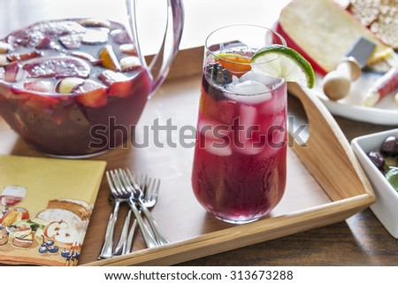 Selective focus was used on this tall glass of refreshing red sangria.  It is filled with a variety of healthy fresh fruits and served with cheese and crackers and other delicious hors Dâ??oeuvres. - stock photo