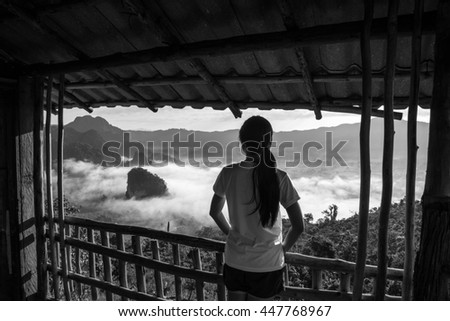 selective focus Woman standing in house  looking to  the moutain & mist  at sunrise