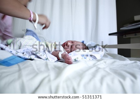 Selective focusing on a new born baby on the hospital bed. - stock photo