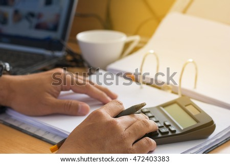Selective focusof man with calculator counting making notes at home, soft focus.savings, finances, economy and home concept