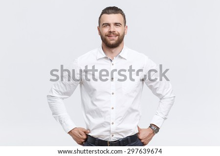 Self-assurance. Smiling handsome man with beard standing with hands on his hips against isolated white background