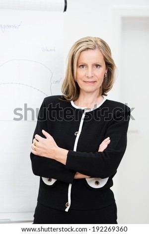 Self-assured attractive middle-aged businesswoman standing with her arms folded looking confidently at the camera with a friendly smile - stock photo