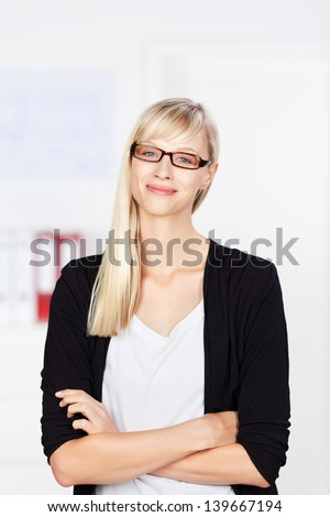 Self-assured businesswoman wearing spectacles standing with her arms folded smiling at the viewer