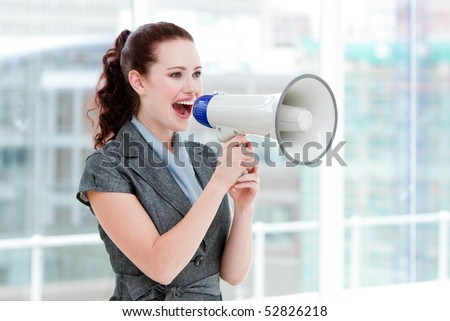 Self-assured businesswoman yelling through a megaphone standing in the office - stock photo
