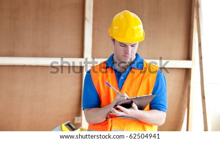 Self-assured male worker writing on a clipboard at work - stock photo