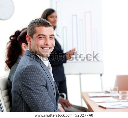 Self-assured young businessman at a presentation with his team - stock photo