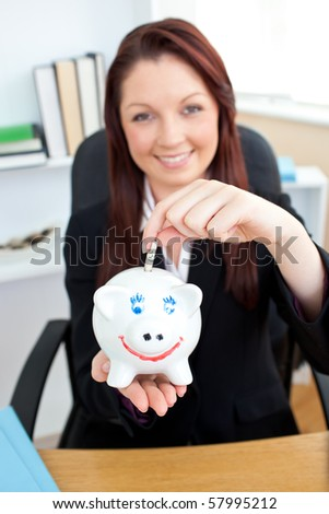 Self-assured young businesswoman putting money in a piggybank siiting in her office - stock photo