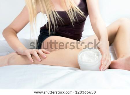 Self caring female applying creme on leg - stock photo