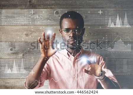 Self-confident black scientist in glasses and pink shirt using futuristic touchscreen display, drawing charts and diagrams, looking at the camera. People and future technology concept. Double exposure - stock photo