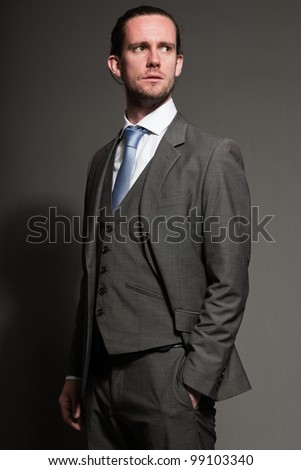 Self confident man brown long hair with expressive face wearing grey suit and blue tie. Isolated on grey background.