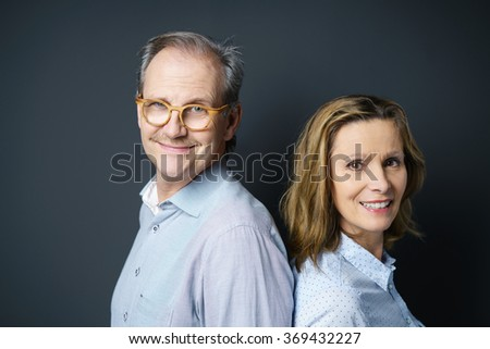 self-conscious couple standing back to back looking at the camera with a smile