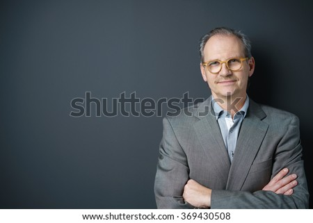 self-conscious middle-aged businessman standing with arms crossed - stock photo
