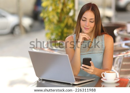 Self employed woman working with her phone and laptop in a restaurant terrace with a cup of coffee - stock photo